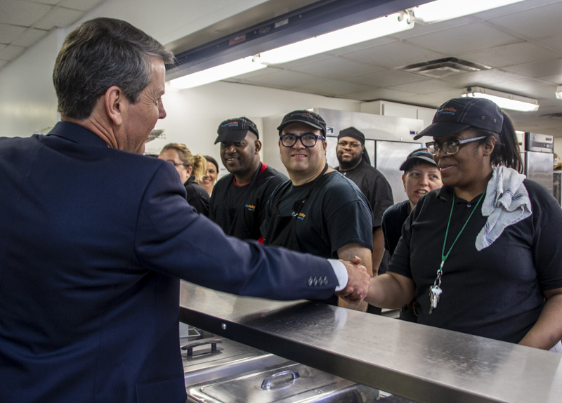 Georgia Governor Brian Kemp shakes hands with Ebony, one of the eleven program participants learning commercial kitchen skills at EmployAbility Catering.