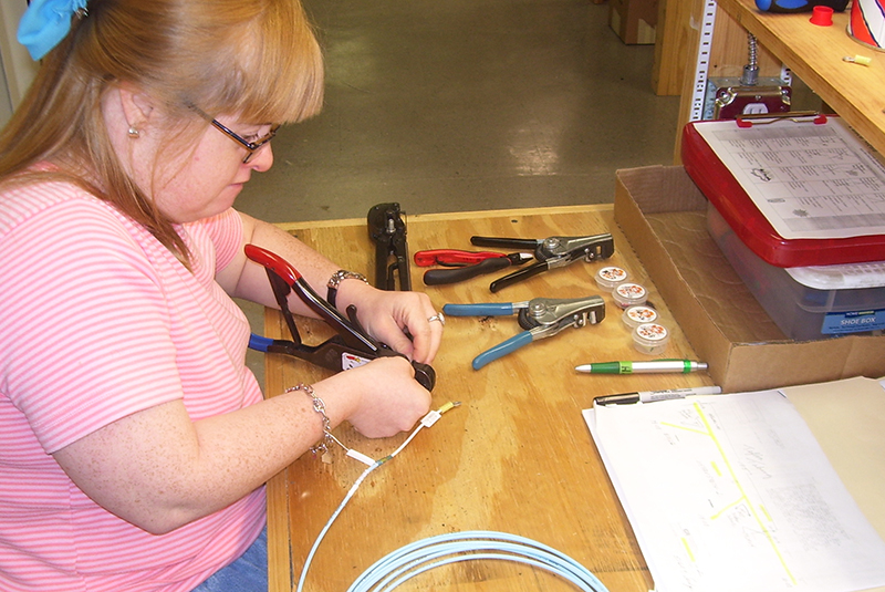 A woman practices small parts assembly