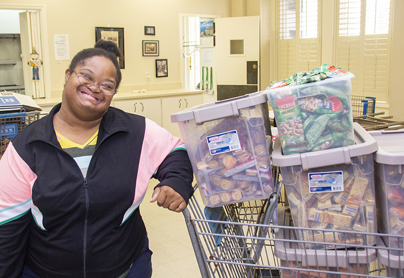 A woman stands next to a cart of food collected and organized to distribute to people experiencing homelessness